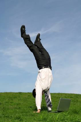 businessman doing handstand and using laptop outdo